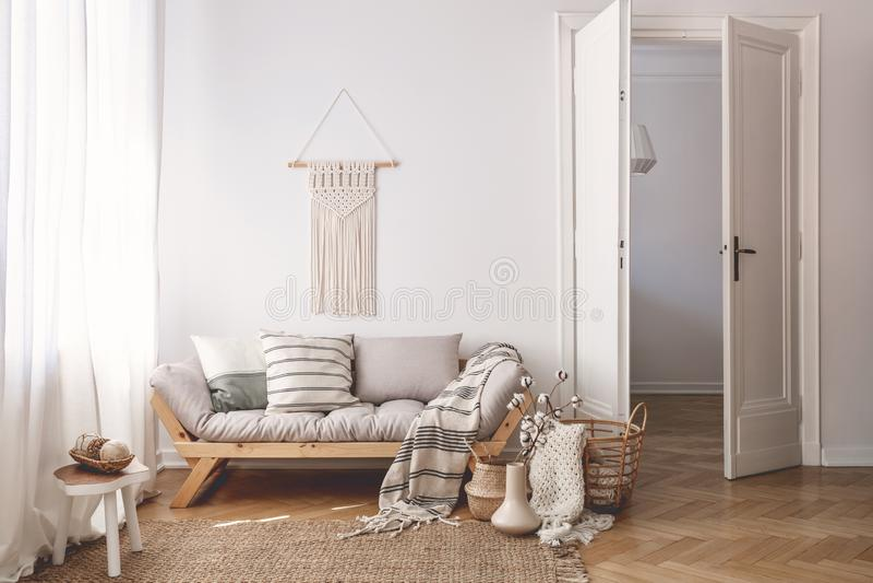 被日光照射了客厅内部与门户开放主义,人字形木条地板地板、自然,米黄纺织品和白色墙壁 免版税库存照片