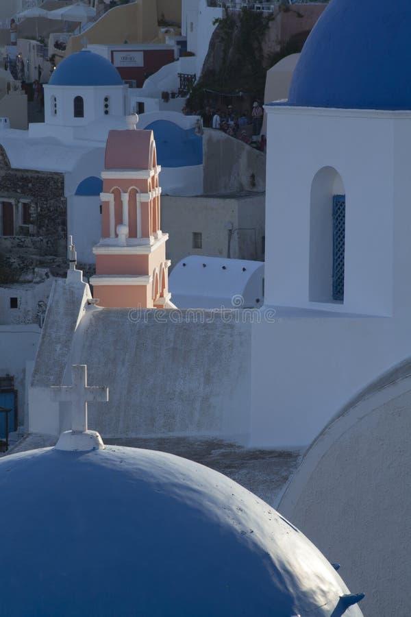 被日光照射了教会尖顶在圣托里尼希腊海岛上的Oia镇  库存图片