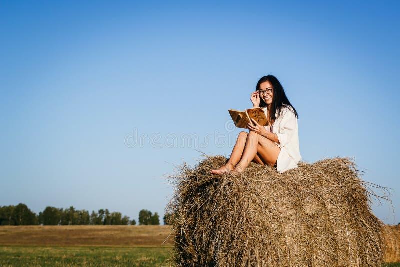 被晒黑的女孩坐干草堆 免版税库存照片