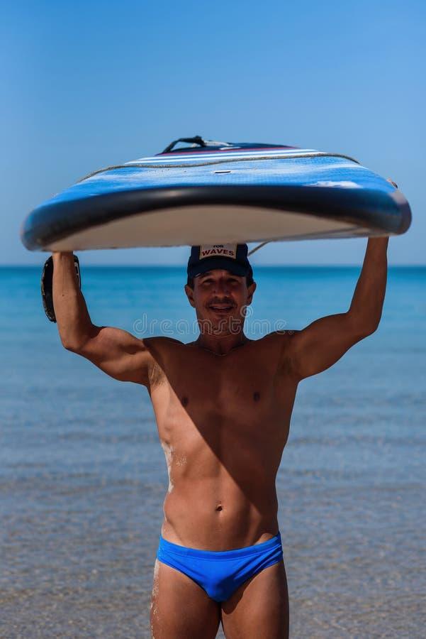 被晒黑的运动的人拿着他的在他的头的冲浪板在海背景 概念是一种运动和健康生活方式 库存图片