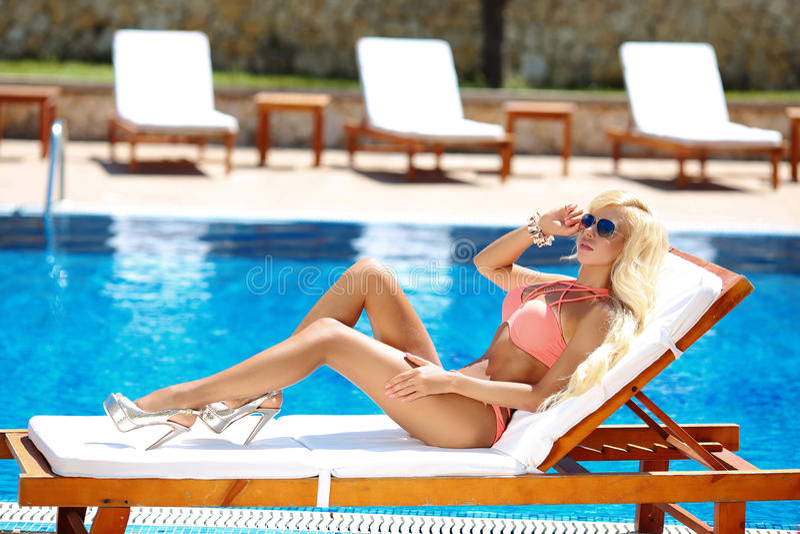 被晒黑和说谎在轻便折叠躺椅的美好的性感的妇女比基尼泳装模型 库存照片