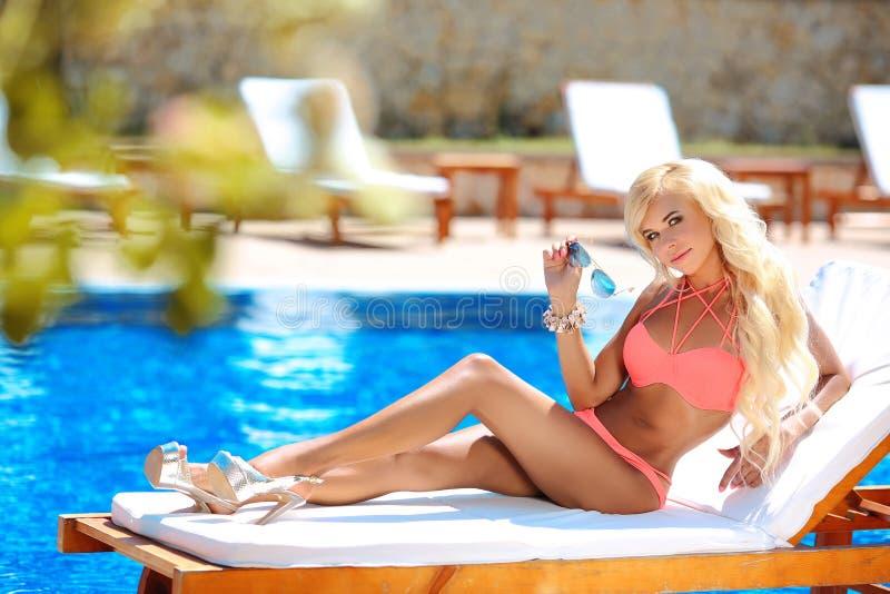 被晒黑和说谎在轻便折叠躺椅的美好的性感的妇女比基尼泳装模型 库存图片