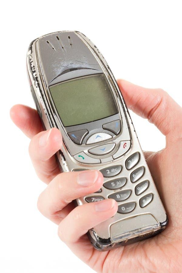 被暂挂在白色的一个老被用完的移动电话 免版税库存图片