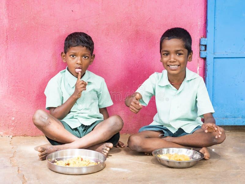 被服务的两个男孩少年学生米膳食板材在政府学校食堂的 可怜的孩子的不健康的食物 库存图片