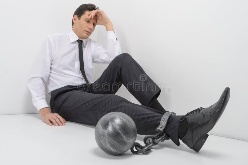 被束缚的商人。全长沮丧的商人sittin 免版税库存图片