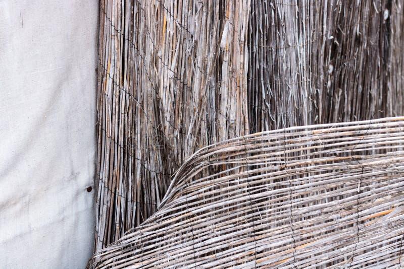 被毁坏的减速火箭的被佩带的篱芭的葡萄酒竹藤条特写镜头相连与生锈的导线和白色织品帆布背景 免版税图库摄影