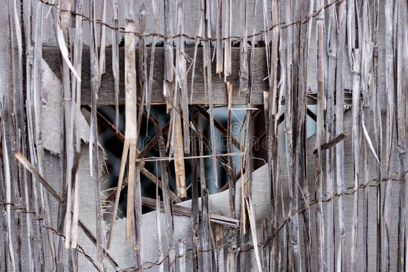 被毁坏的减速火箭的被佩带的篱芭的葡萄酒竹藤条特写镜头,与孔的白色织品帆布和磨损的边缘,在ba的链节 免版税库存图片