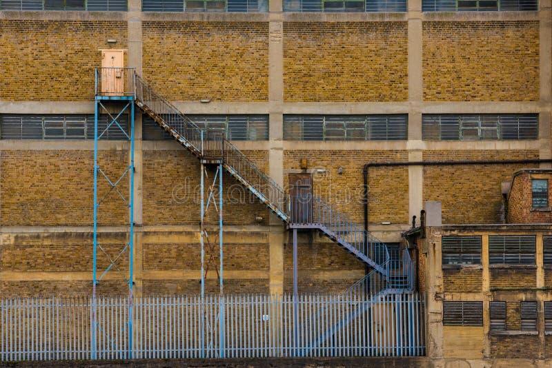 被毁坏的工厂厂房外部门面与火esc的 免版税库存图片