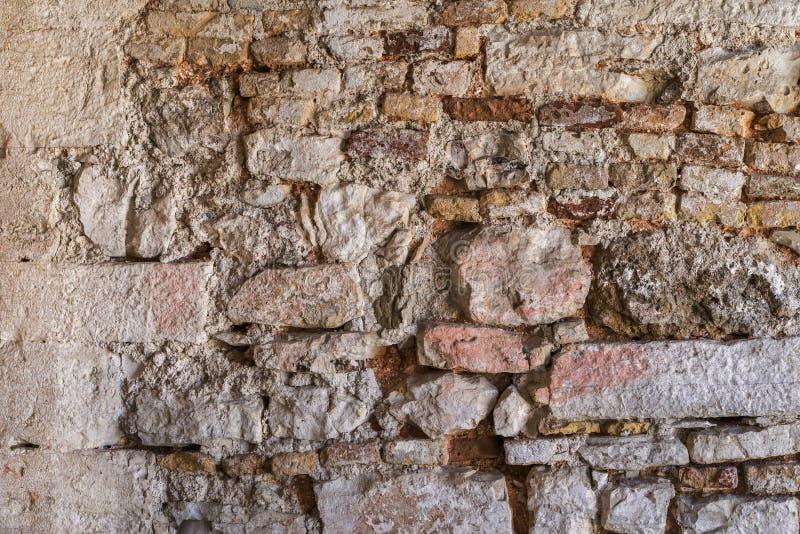 被毁坏的石砖墙的老七高八低的纹理 库存照片