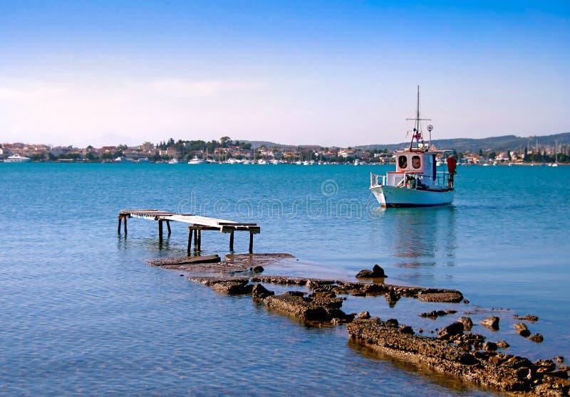被毁坏的码头和白色小木渔船 库存图片