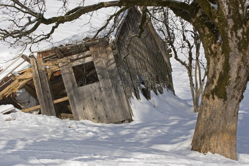 被毁坏的高山小屋在冬天 免版税库存图片