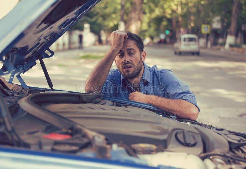 被注重的人有与看在失望不合格的引擎的残破的汽车的困难 免版税图库摄影