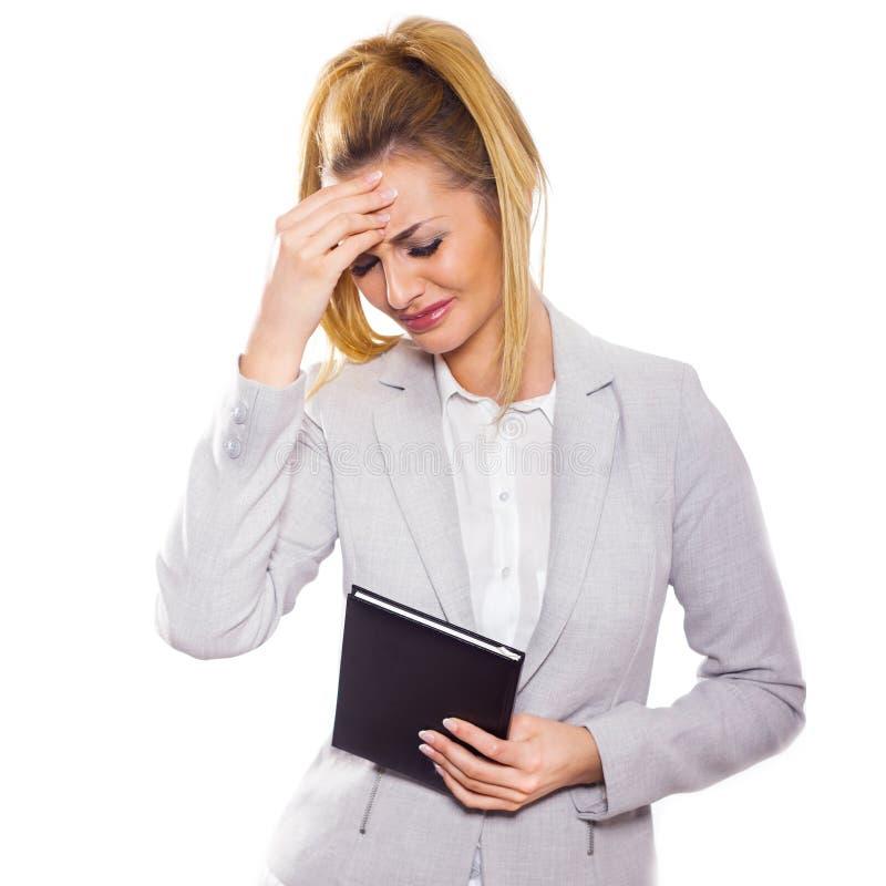 被注重的女实业家用她的在白色背景隔绝的前额的手。 图库摄影
