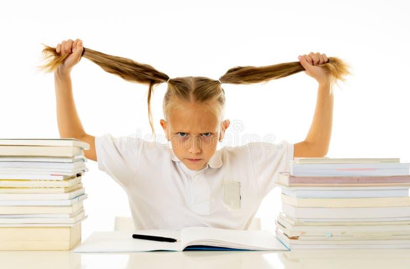被注重的女小学生淹没与许多所家庭作业hatting的学习和学校 免版税图库摄影