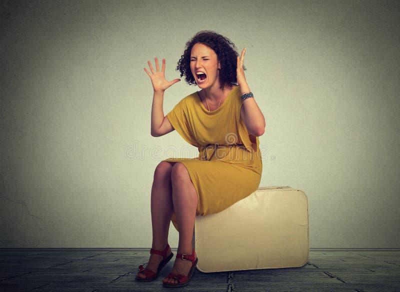 被注重的妇女坐手提箱尖叫在失望 免版税库存照片