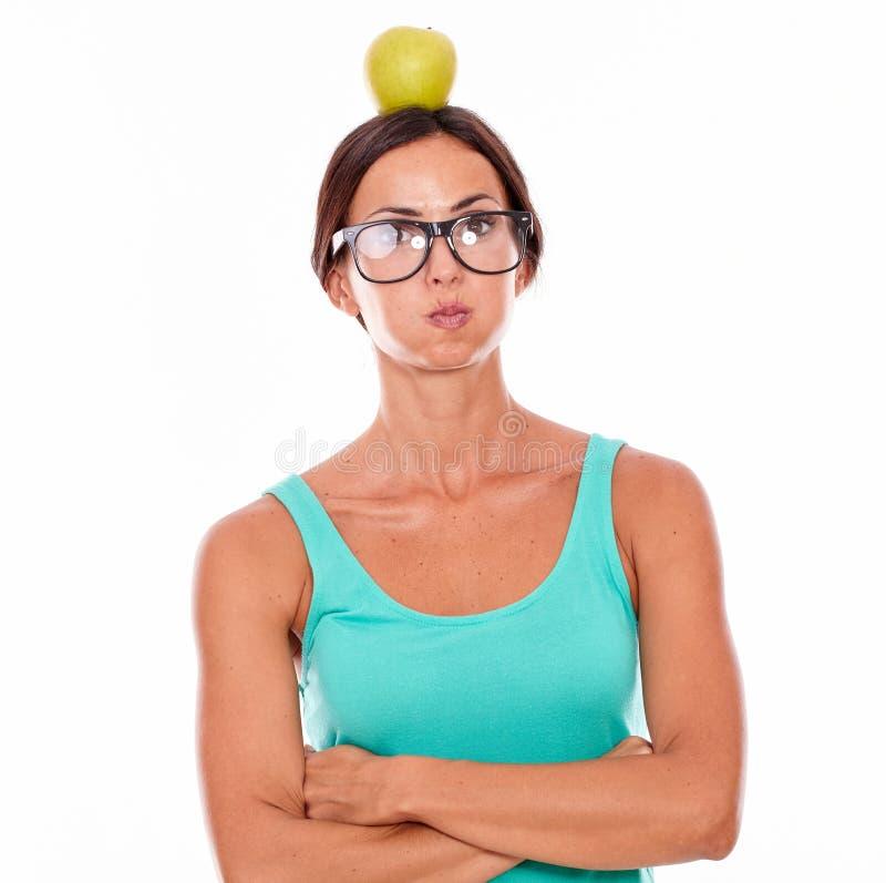 被注重的妇女用在她的头的一个苹果 图库摄影