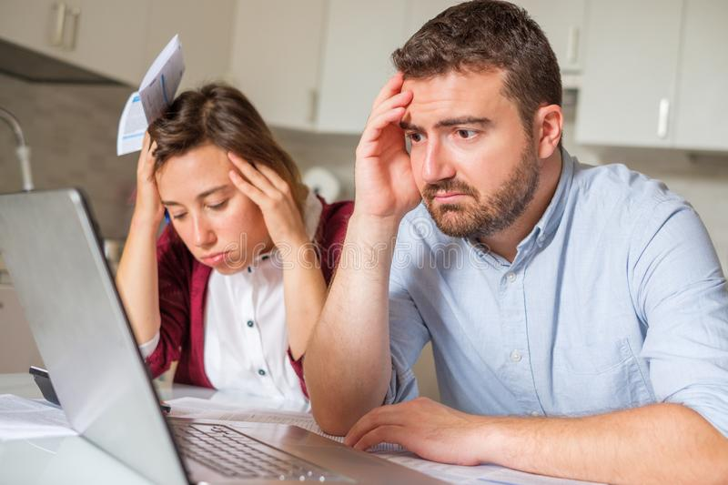 被注重的妻子和丈夫有计算家庭公司的许多债务的 库存图片