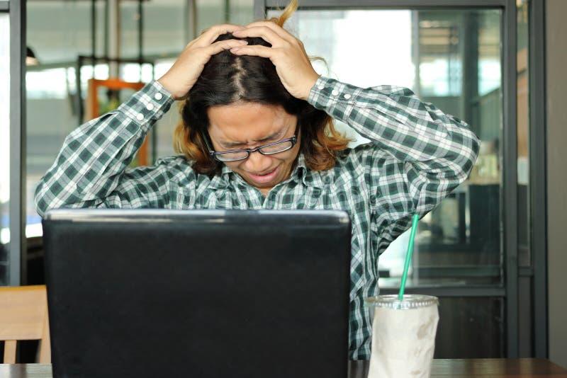 被注重的年轻亚裔商人用在顶头感觉的手疲倦了反对他的工作在办公室 被用尽的和劳累过度工作概念 免版税库存照片