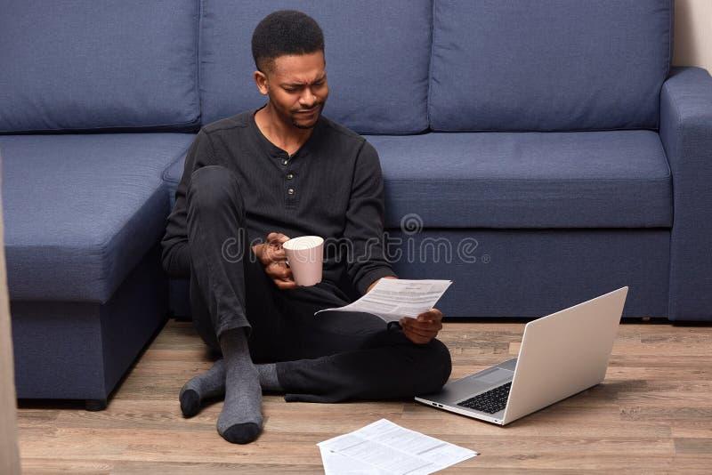 被注重的生气人坐地板藏品在两只手中起来了有饮料的杯子和文件,读殷勤地,使用他的膝上型计算机 免版税库存照片