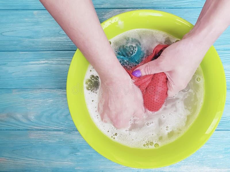 被洗举行在一个水池的妇女手家庭泡沫服务在木背景的蓝色 库存照片