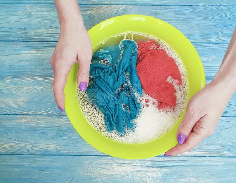 被洗举行在一个水池的妇女手服务在木背景的蓝色 库存图片