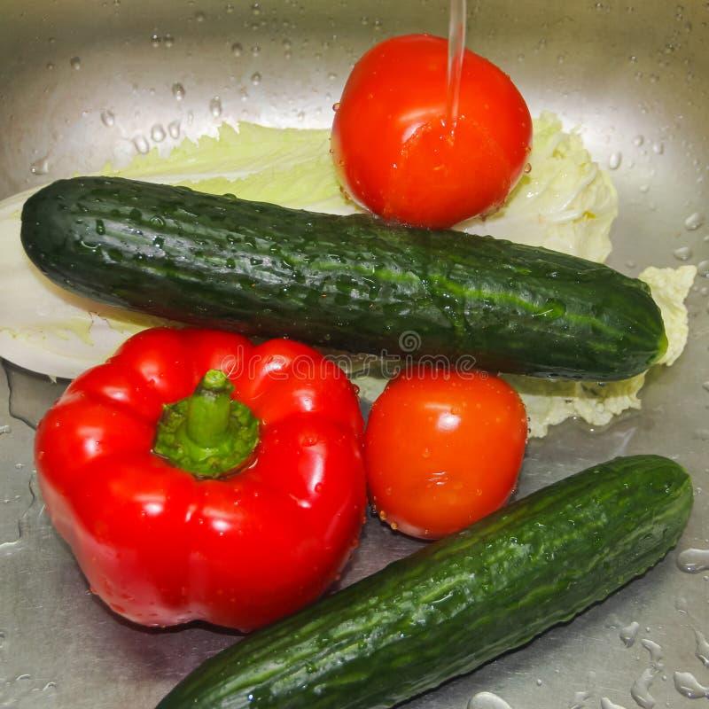 被洗涤的蔬菜 在自来水下的菜在罪孽 免版税库存照片