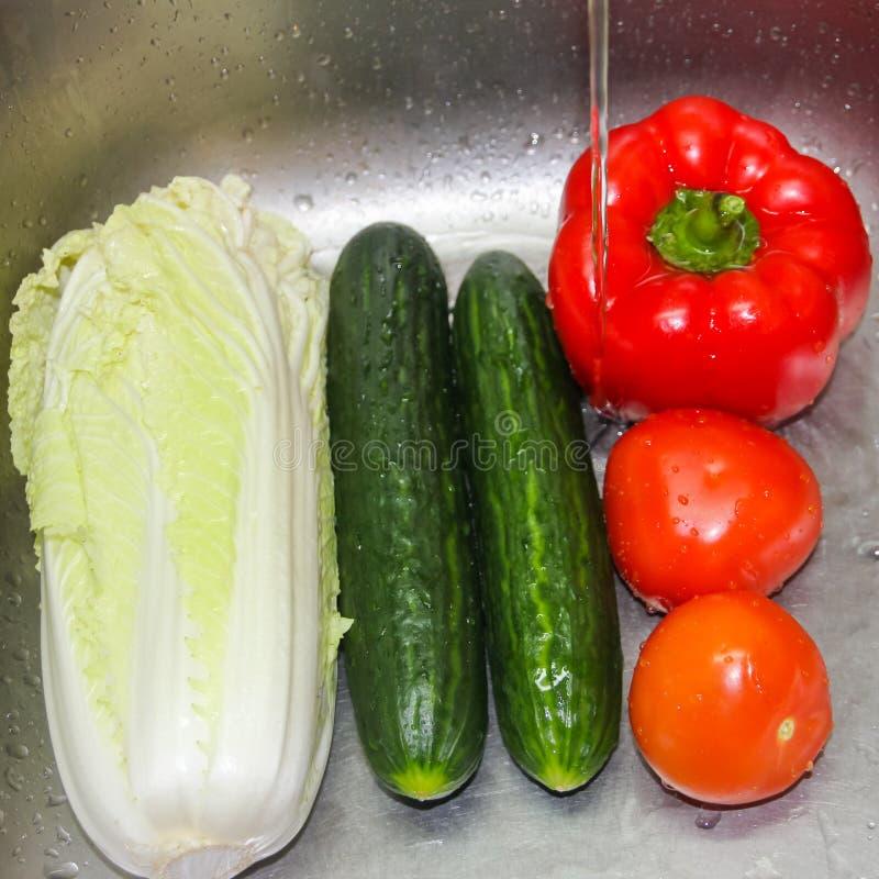 被洗涤的蔬菜 在自来水下的菜在罪孽 免版税库存图片