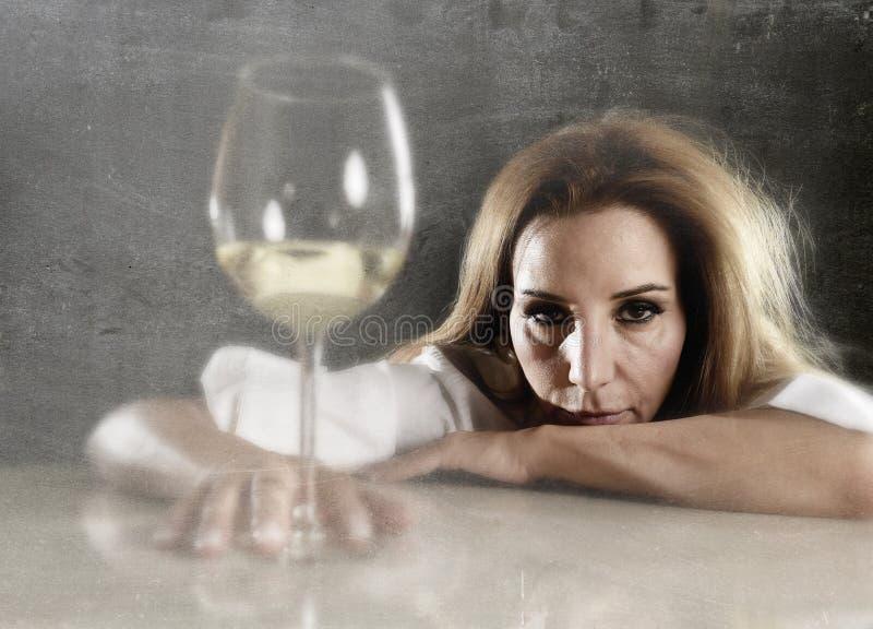 被浪费的醺酒的妇女压下了看起来体贴与白葡萄酒玻璃 免版税库存照片