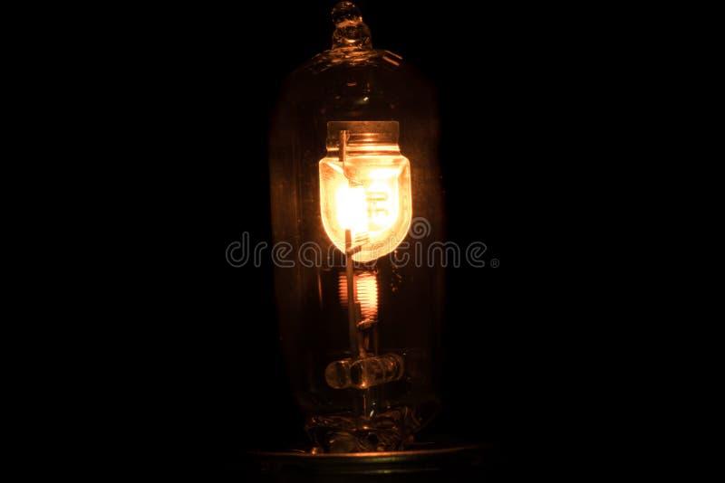 被浸洗的和主梁车灯的白炽灯有燃烧的螺旋的在黑背景 图库摄影