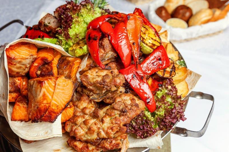 被混合的格栅肉、油煎的菜和烤三文鱼鱼片在温暖的盘的装饰 免版税库存照片