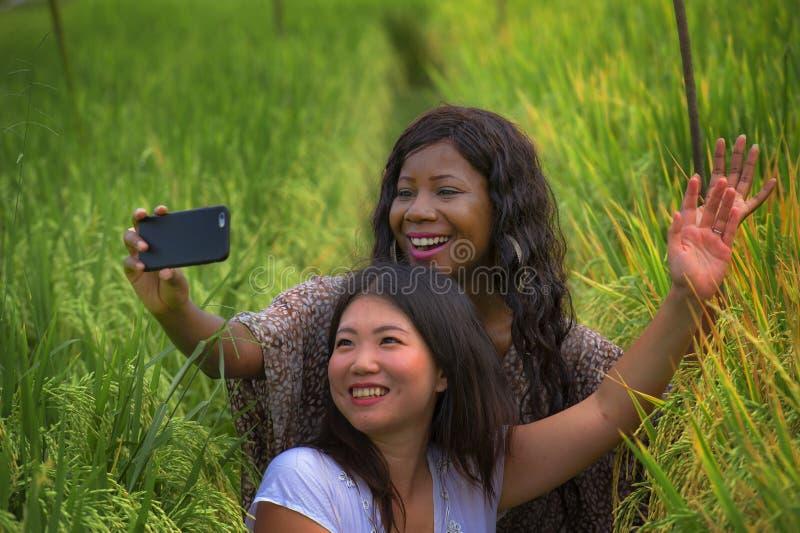 被混合的种族亚裔中国采取女朋友与手机的女孩和黑人非裔美国人的妇女
