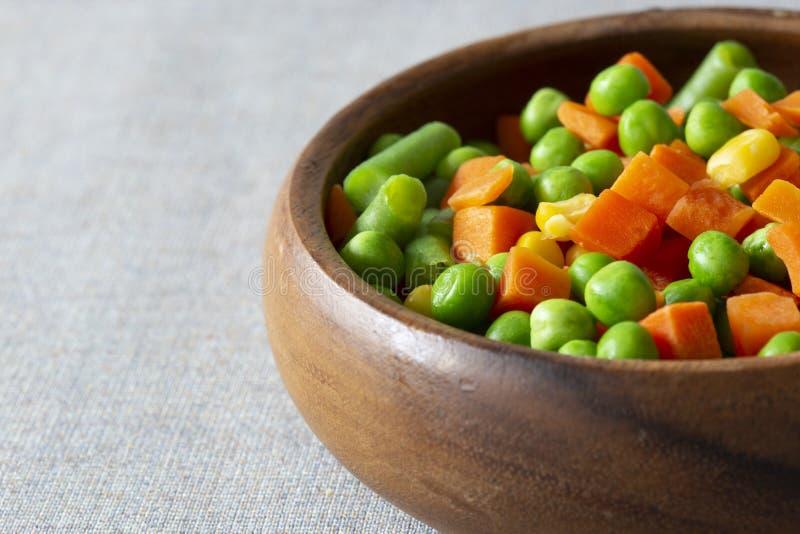 被混合的菜,用红萝卜、豆、豌豆和甜玉米,在一个木碗 在一张灰色桌布 免版税库存照片