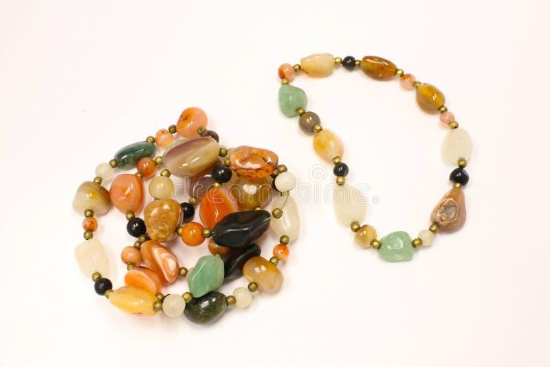 被混合的颜色镯子和项链首饰由自然石头制成 免版税库存照片