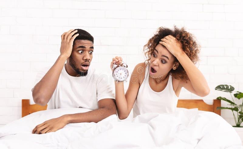 被混淆的夫妇在床上错过了敲响闹钟 库存图片