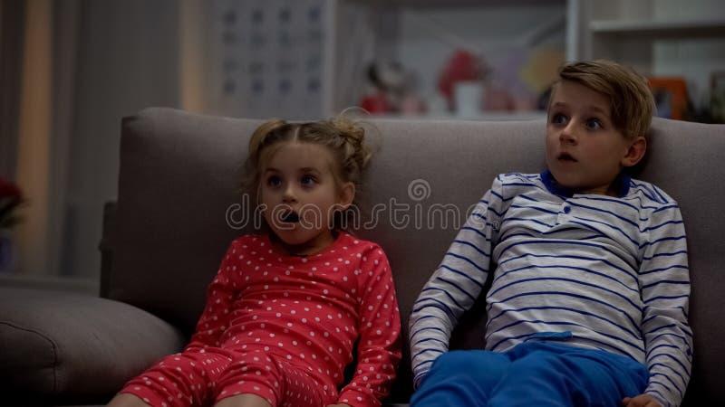 被淹没的兄弟和姐妹观看的恐怖电影在晚上,坐的沙发 免版税库存图片
