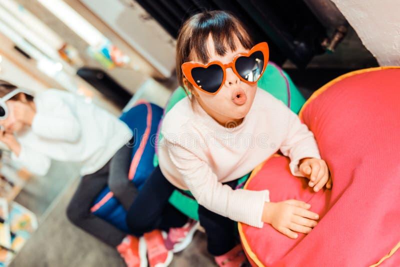 被激发与她新的时髦的太阳镜的活跃深色头发的孩子 免版税库存图片