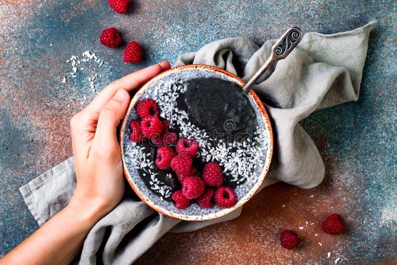 被激活的木炭圆滑的人和chia种子布丁碗、素食主义者戒毒所点心用莓和椰奶 顶上,顶视图 图库摄影