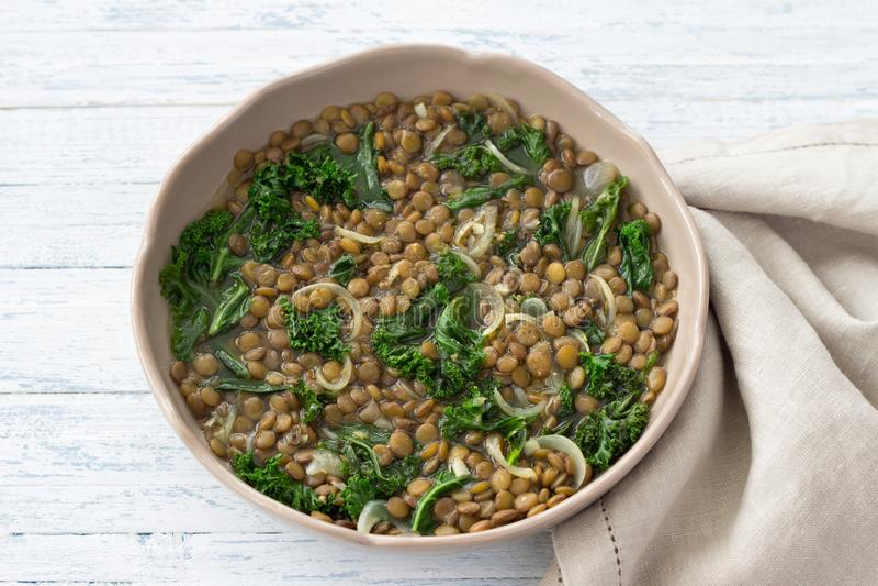 被炖的无头甘蓝扁豆用葱和大蒜在轻的背景 免版税库存照片