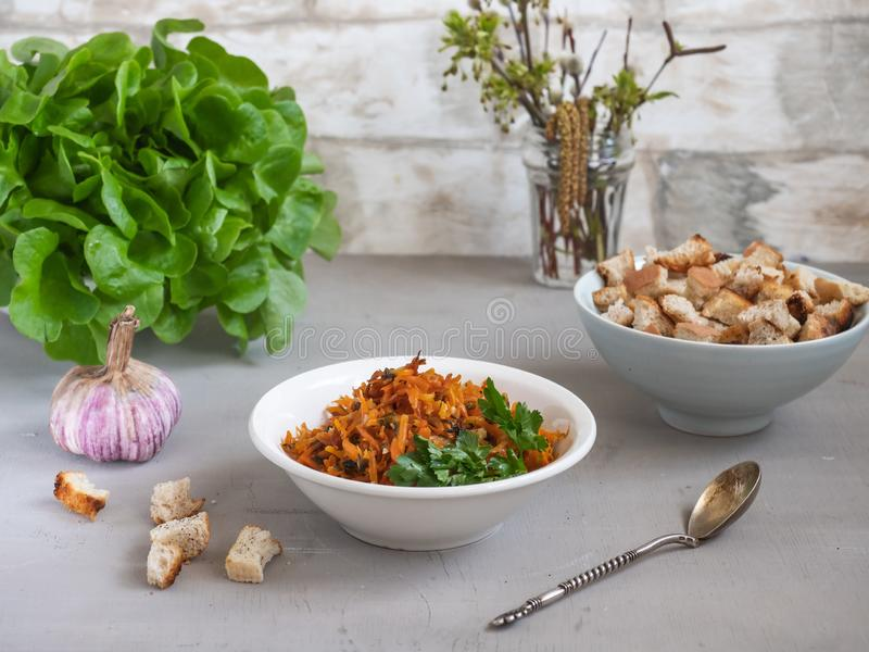 被炖的红萝卜用荷兰芹和大蒜在一块深板材用薄脆饼干和叶茂盛补丁一顿清淡的素食者快餐在背景中, 图库摄影