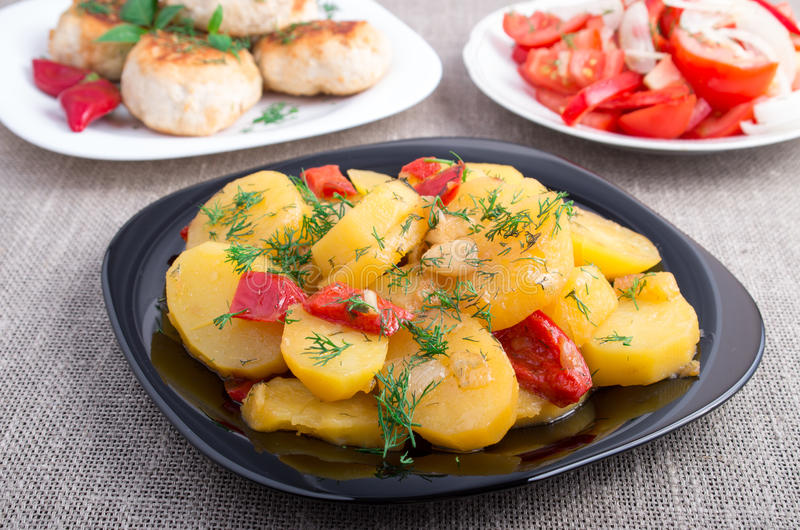被炖的肉末土豆、丸子和蕃茄沙拉 免版税库存照片