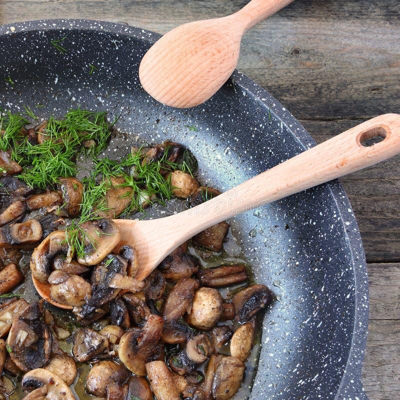 被炖的蘑菇在粗砺的木头的一个煎锅服务与新蓬蒿和莳萝绿色 好的妙语Appetit! 免版税库存照片