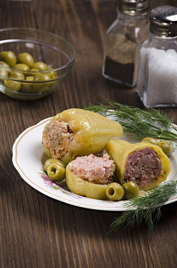 被炖的青椒充塞用在木背景的肉,用橄榄和盐在烧瓶,45图,垂直的射击 免版税库存图片