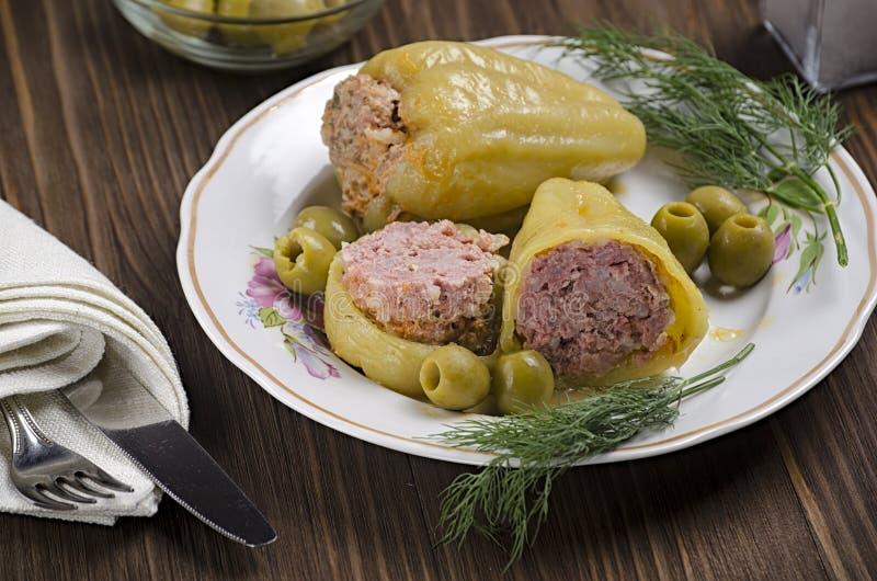被炖的青椒充塞用在木背景的肉,用橄榄和盐在烧瓶,45图 免版税库存照片