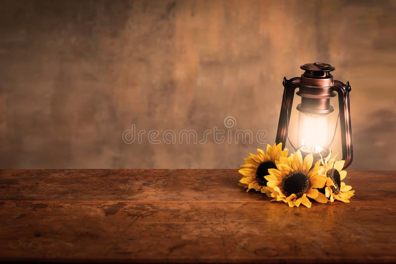 被点燃的古色古香的灯笼背景用向日葵 免版税库存图片