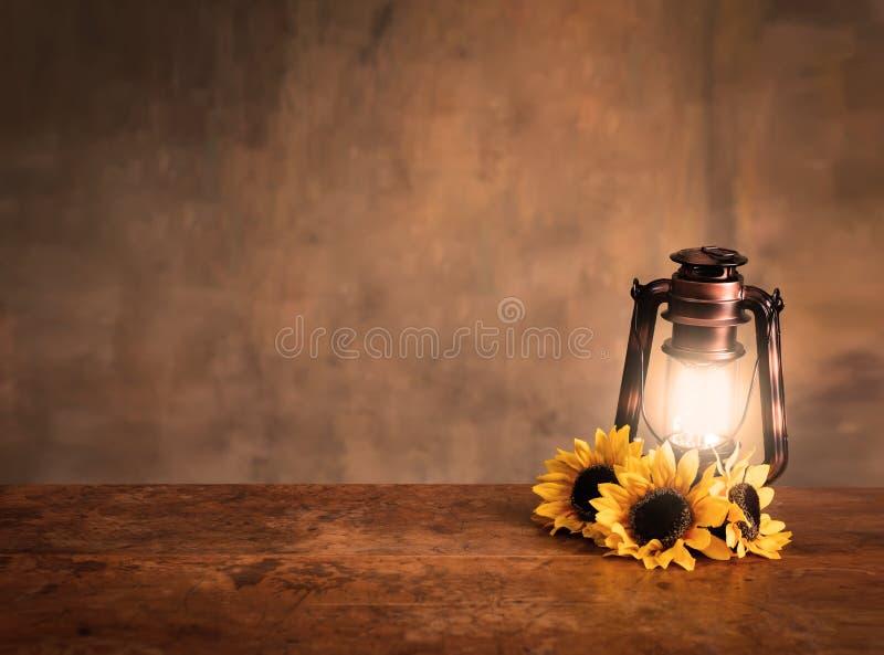 被点燃的古色古香的灯笼背景用向日葵 库存图片