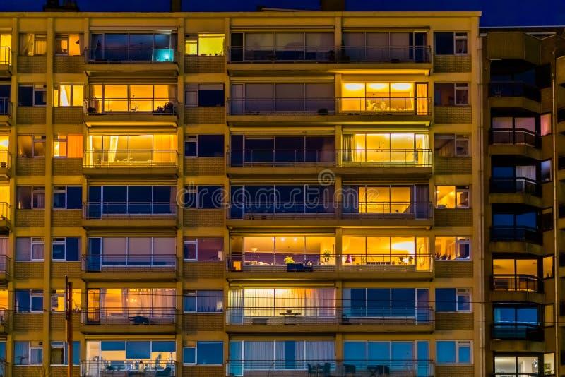被点燃的城市公寓在夜、比利时城市建筑学与窗口和阳台之前 免版税库存照片