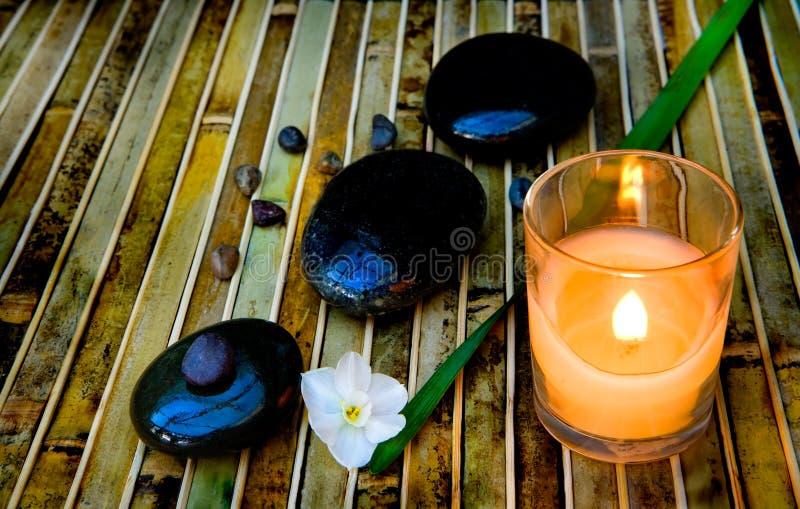 被点燃的蜡烛向禅宗扔石头 库存图片