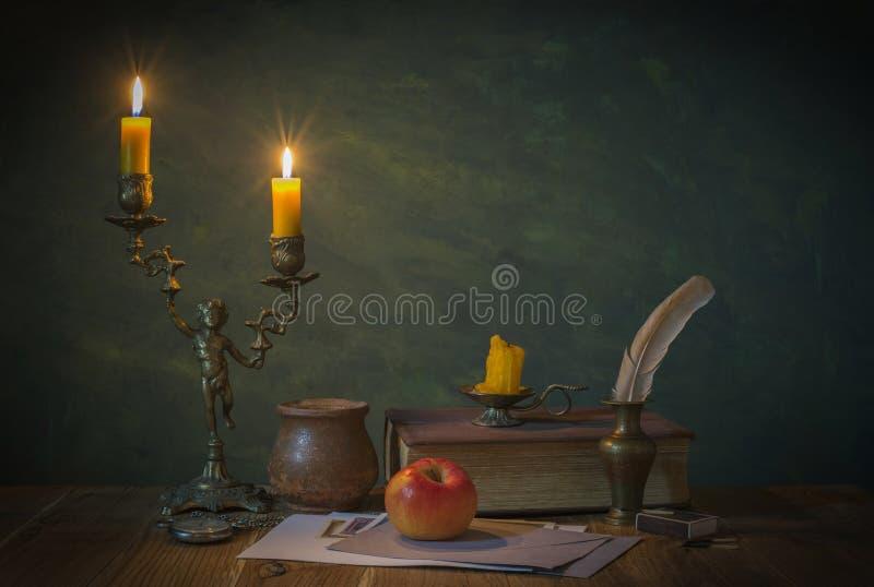 被点燃的蜡烛和书 图库摄影