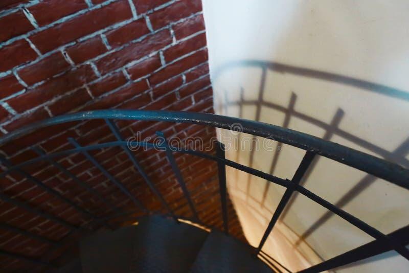 被炼的铁扭转了有反射的台阶在红砖墙壁上,老葡萄酒大厦,艺术的扶手栏杆 免版税库存照片