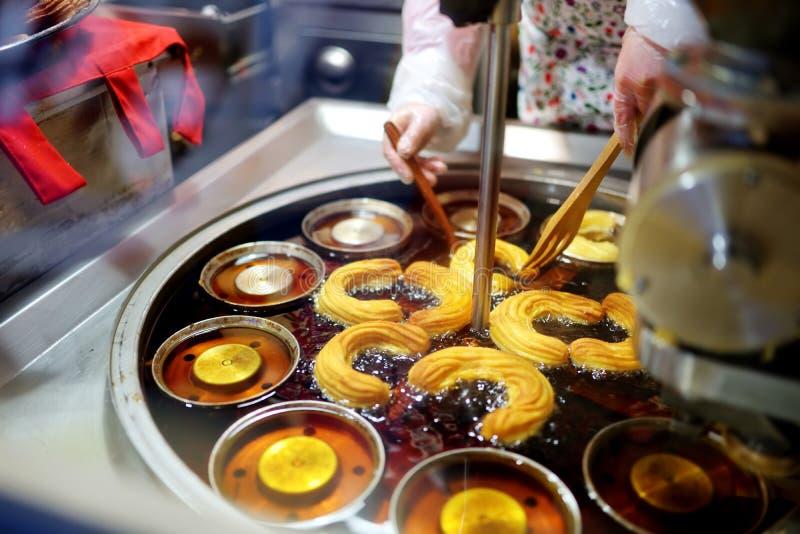 被烘烤一致的可口churros在圣诞节市场上的摊位在维尔纽斯,立陶宛 库存图片